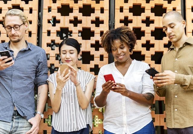 Imagem de pessoas usando celular simbolizando alcance das publicações