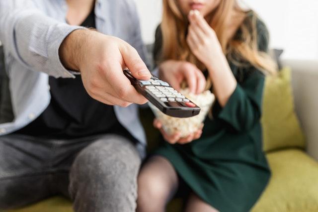 Imagem de casal com controle remoto na mão para exemplificar alcance