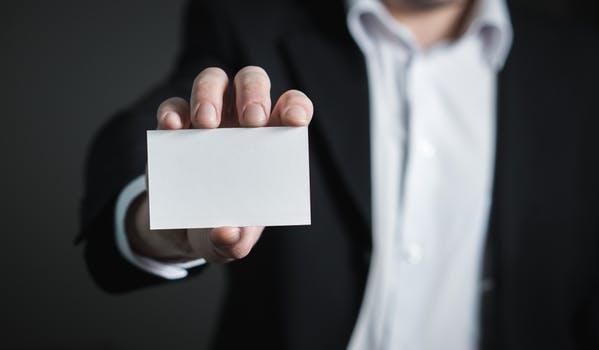 Pessoa segurando cartão de visitas em branco simbolizando biografia