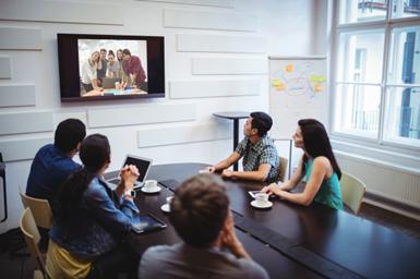 Grupo de pessoas em volta de tela assistindo webinar