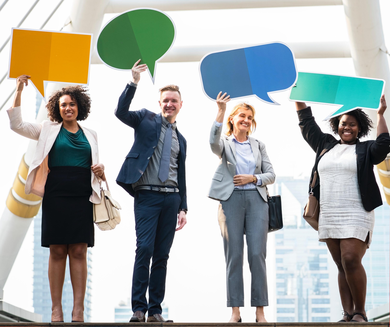 Foto de pessoas segurando balões de comentários ilustrando as avaliações online